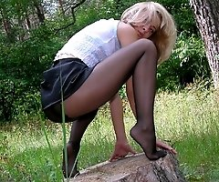 Juicy slut in the wood showing what she's got hidden underneath her skin-tight black nylons